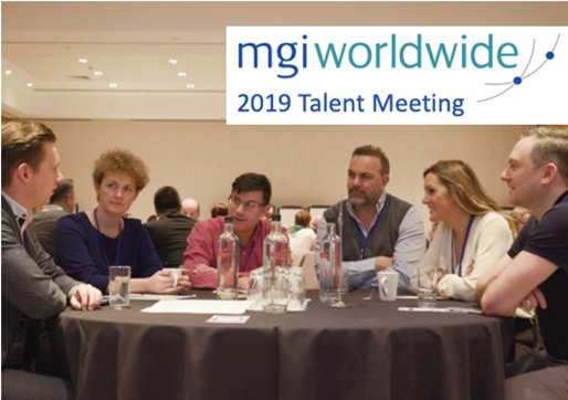 MGI World Image of delegates sitting at table at Talent Meeting with MGI Worldwide logo